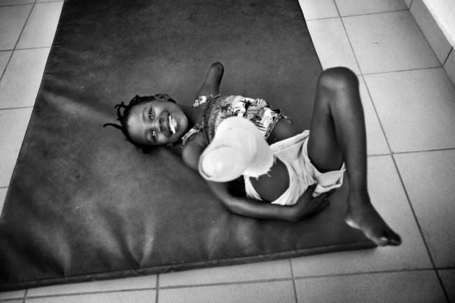 Ein Mädchen ohne Arm und ohne Bein liegt auf einer Matte und lacht in die Kamera.