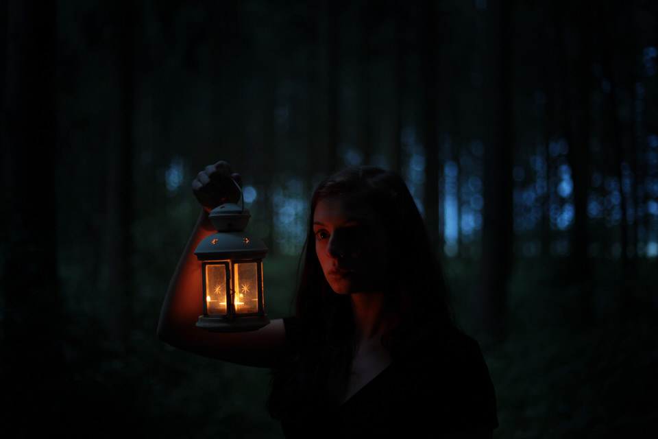 Eine Frau mit einer Laterne im Wald.