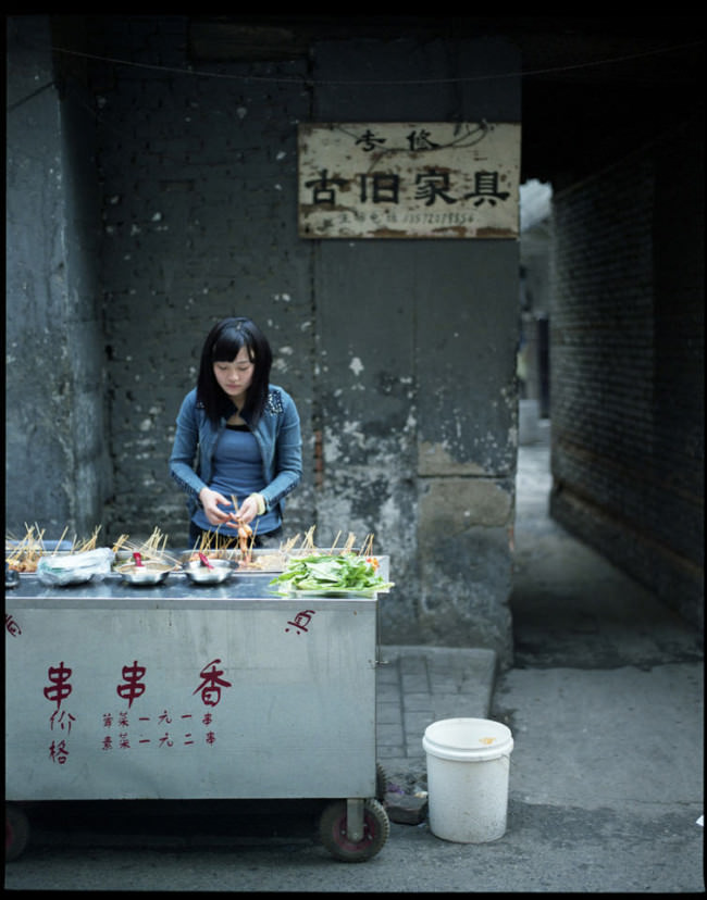 Eine junge Frau verkauft Essen an einem Straßenimbiss