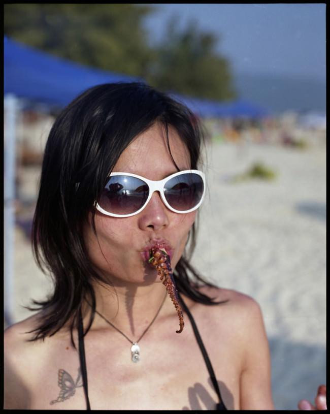 Portrait einer Frau mit Sonnenbrille und Tintenfisch im Mund