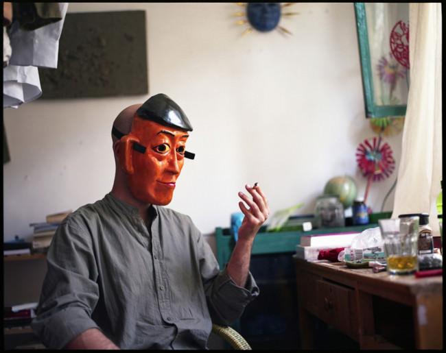 Portrait eines rauchenden Mannes mit Maske