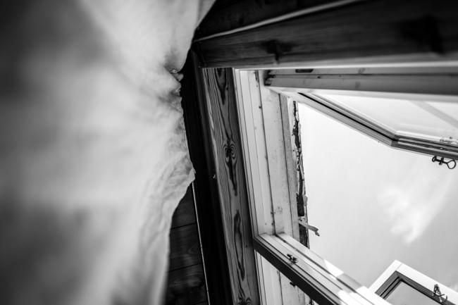 Blick nach oben: Vorhang und ein geöffnetes Fenster.
