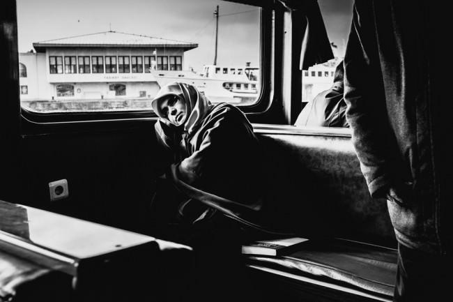 Eine Frau lehnt sich in der Bahn ans Fenster.