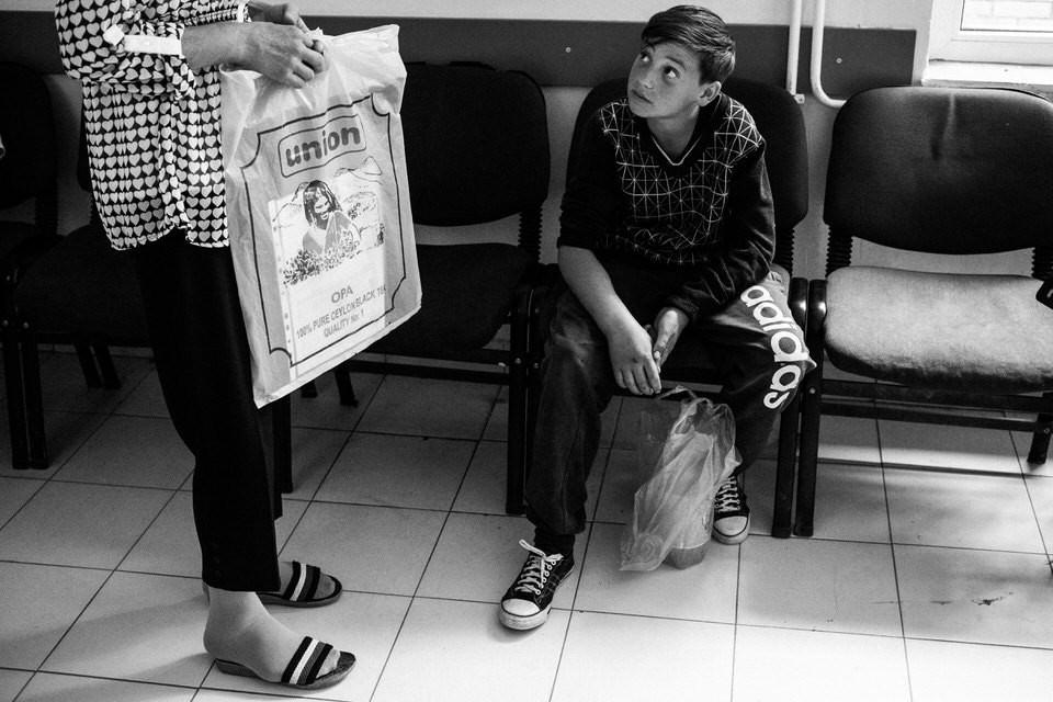 Ein Junge schaut zu einer Frau auf und sitzt auf einem Stuhl.
