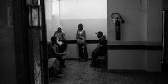 Menschen warten in einem schwach beleuchteten Raum.