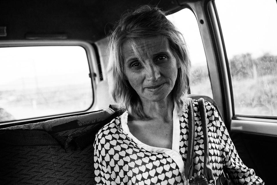 Eine Frau im Jeep schaut in die Kamera.