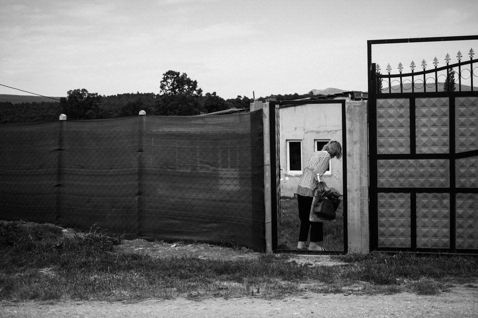 Eine Frau öffnet ein Tor vor einem Haus.