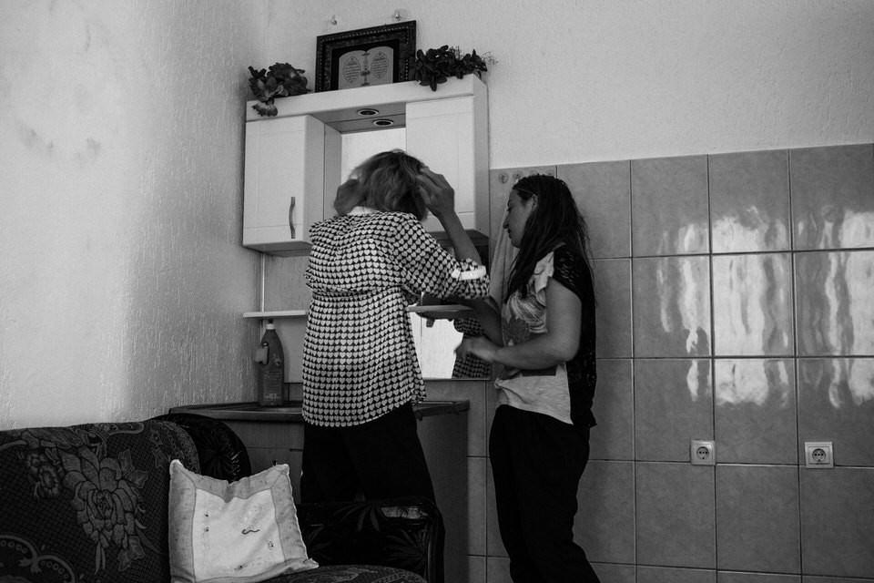 Eine Frau macht sich vor dem Spiegel schick.
