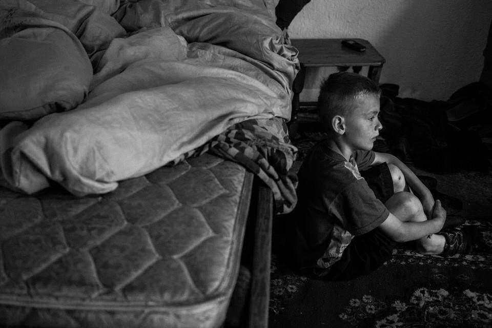 Ein Junge sitzt vor einem Bett.