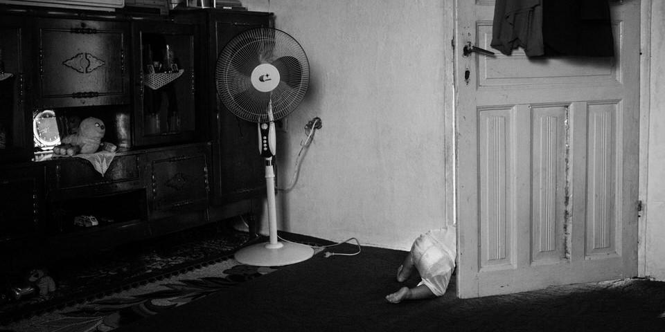 Ein Kleinkind verschwindet hinter einer Tür.