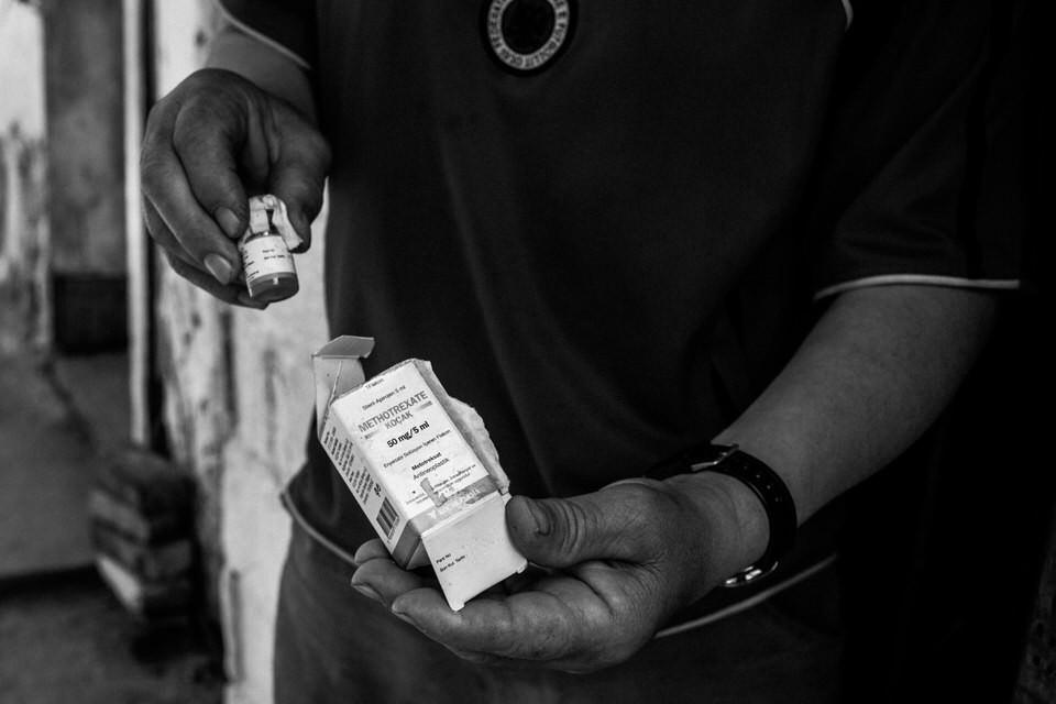 Ein Mann hält ein Medikament in der Hand.