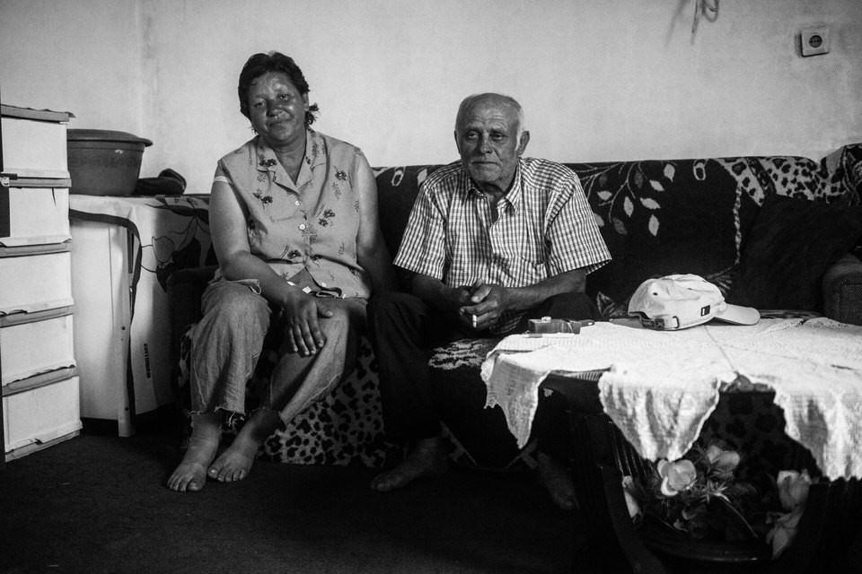 Ein älteres Ehepaar sitzt auf der Couch.