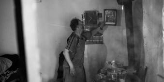 Ein Mann zeigt auf ein Foto, das an der Wand hängt.