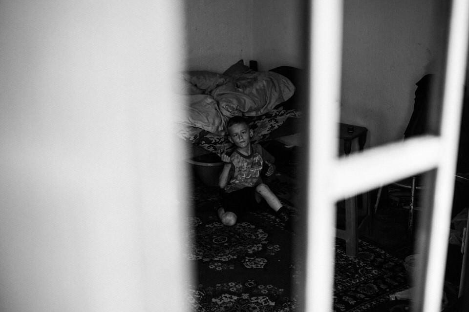 Ein Junge sitzt vor seinem Bett, fotografiert durchs Fenster