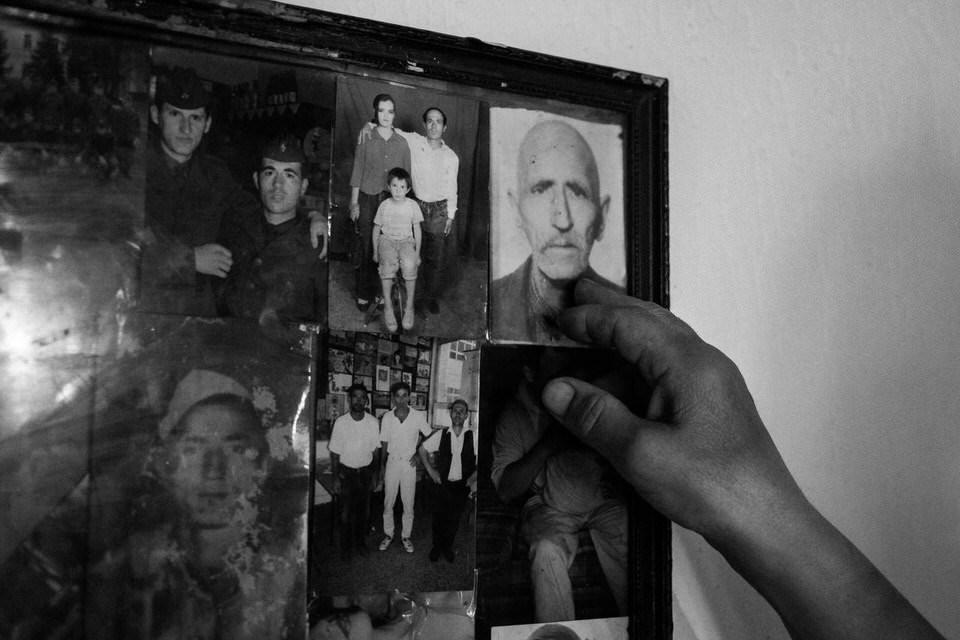 Eine Hand zeigt auf ein Foto, das mit anderen  eingerahmt ist.