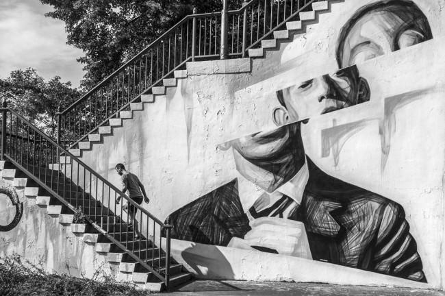Ein Mann läuft eine Treppe hoch, die ein schönes Gemälde trägt.