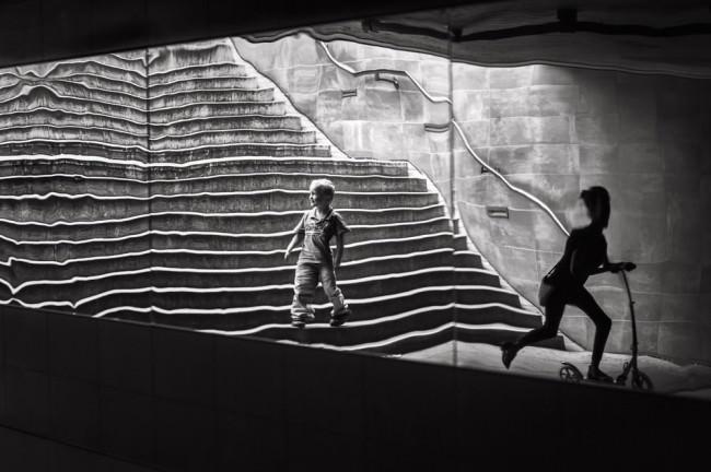 Spielbild zwei spielender Jungen vor einer Treppe.