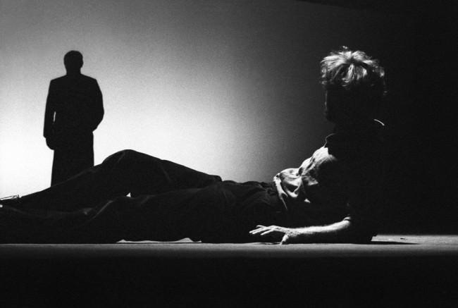 Ein Mann liegt auf dem Boden und schaut einer Silhouette nach.