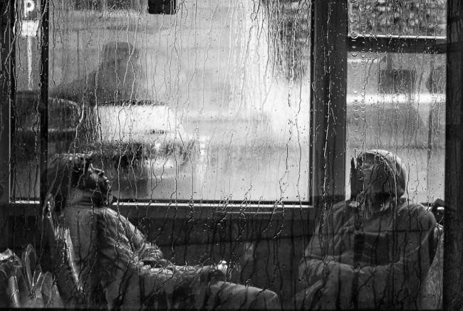 Schlafende Fahrgäste hinter einer nassen Glasscheibe.