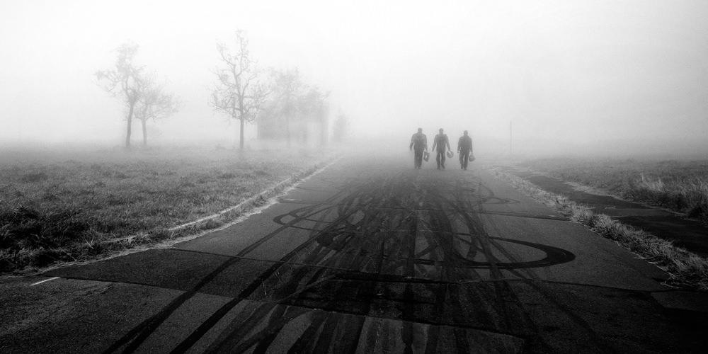 Drei Menschen am Ende einer vernebelten Straße.
