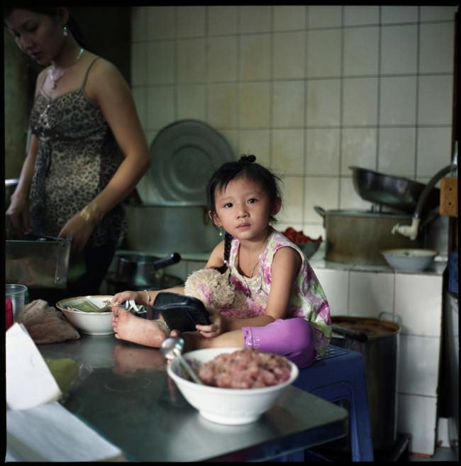 Ein kleines Mädchen sitzt in einer Küche