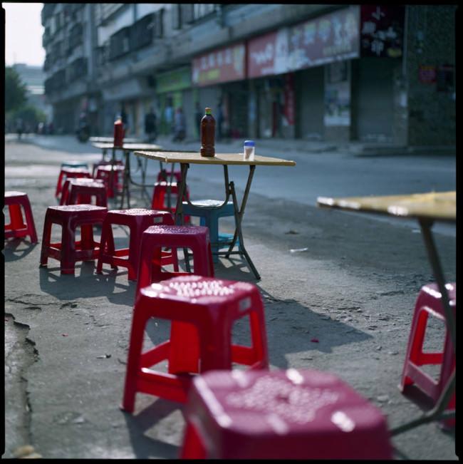 Tische und Plastikhocker auf einer Straße