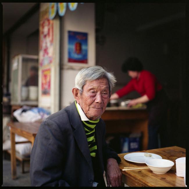 Ein älterer Herr sitzt am Tisch und wartet auf sein Essen.