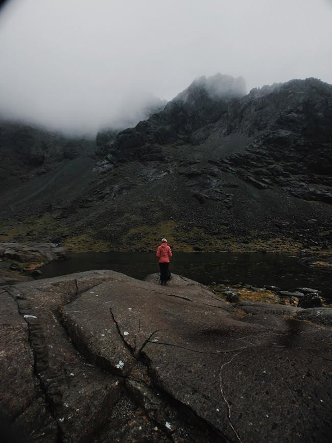 Landschaftsfoto aus Schottland mit einer Person in roter Jacke.