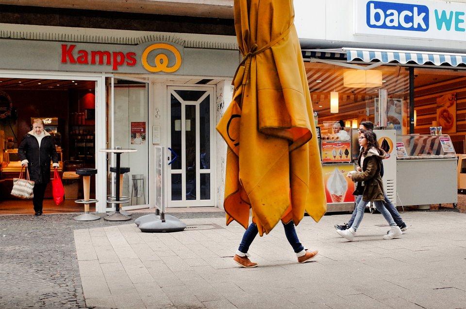 In der Fußgängerzone: Zwei Beine schauen unter einem geschlossenen Sonnenschirm hervor.