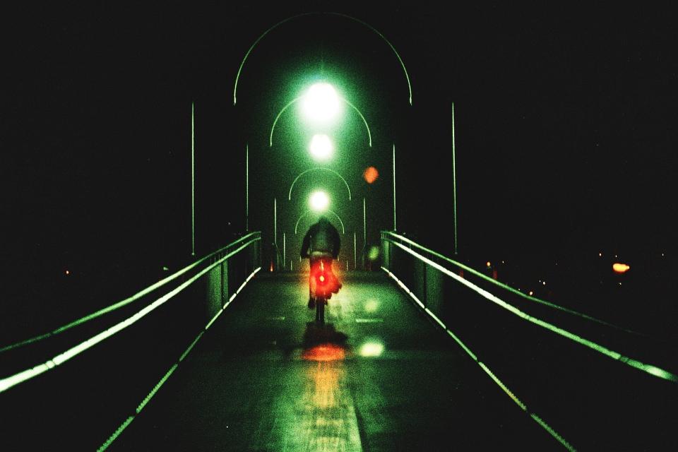 Radfahrer in grünen und roten Lichtern auf einer Brücke in der Dunkelheit.
