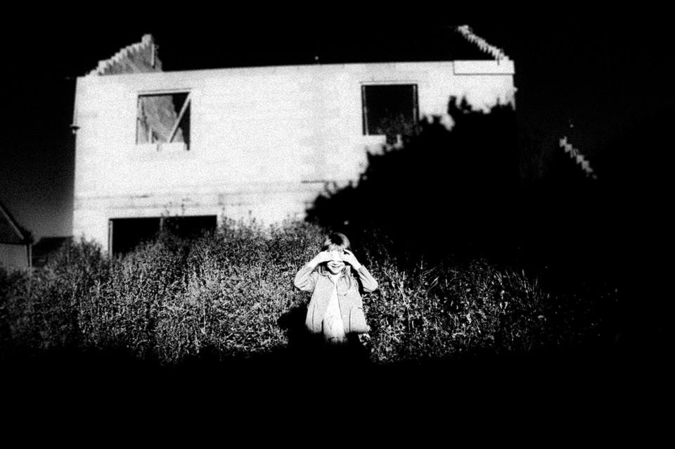 Ein Kind steht vor einem Haus.