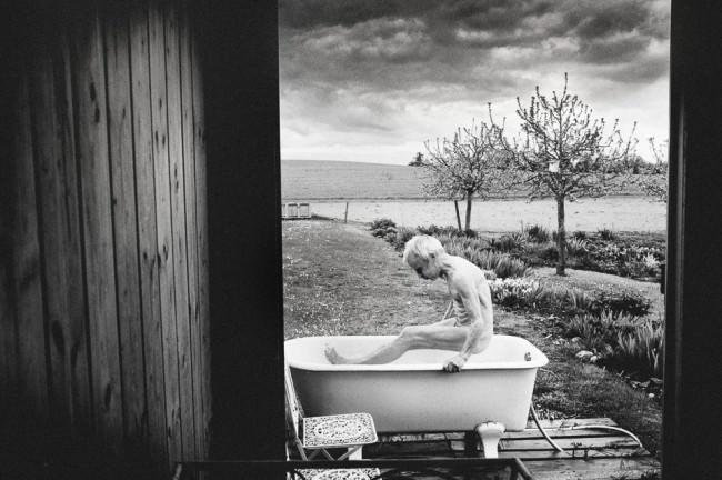 Eine alte Frau steigt in die Badewanne.