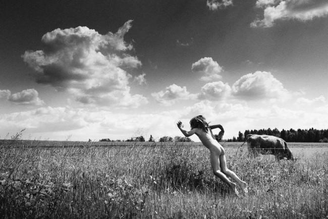 Ein Junge springt in ein Feld.