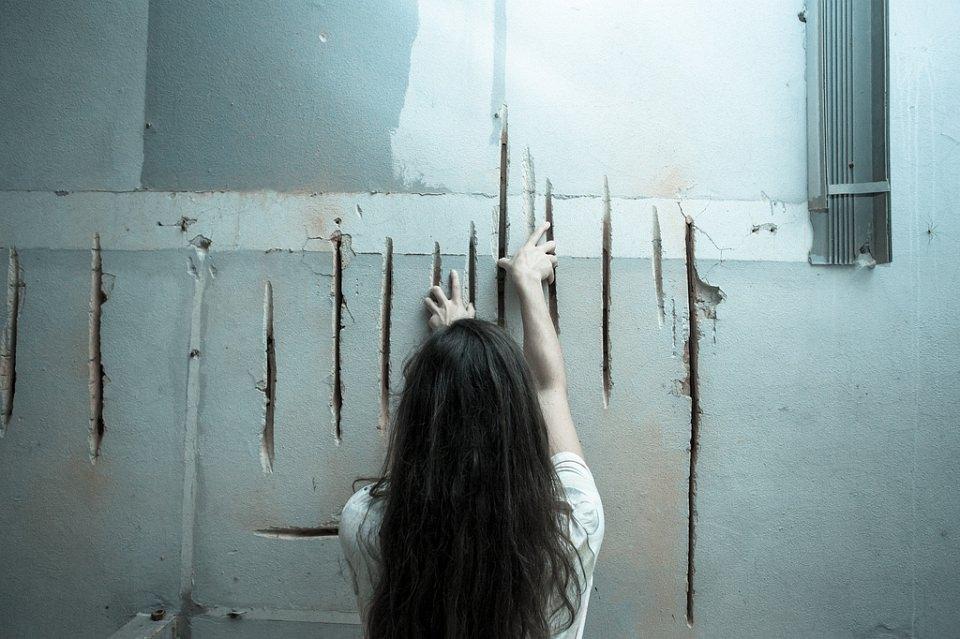 Ein Mädchen fährt mit ihren beiden Händen tiefe Furchen in einer Betonwand nach.