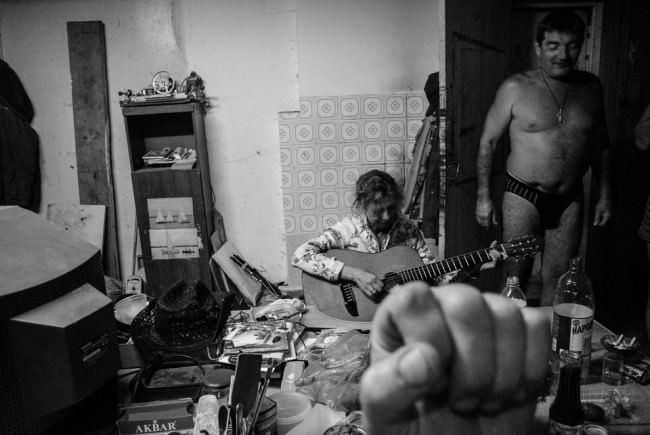 Eine Faust vor der Kamera, eine Frau, die Gitarre spielt und ein Mann mit nacktem Oberkörper.