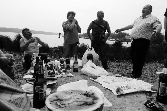 Männer machen Picknick an einem Fluß.