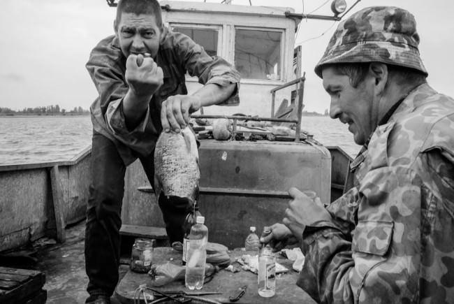 Fischer trinken Vodka und haben Spaß dabei.