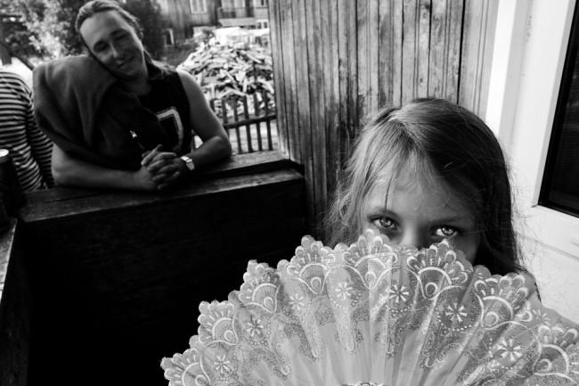 Ein Mädchen mit Fächer schaut in die Kamera.