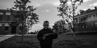 Ein Junge mit Pistole schaut in die Kamera.