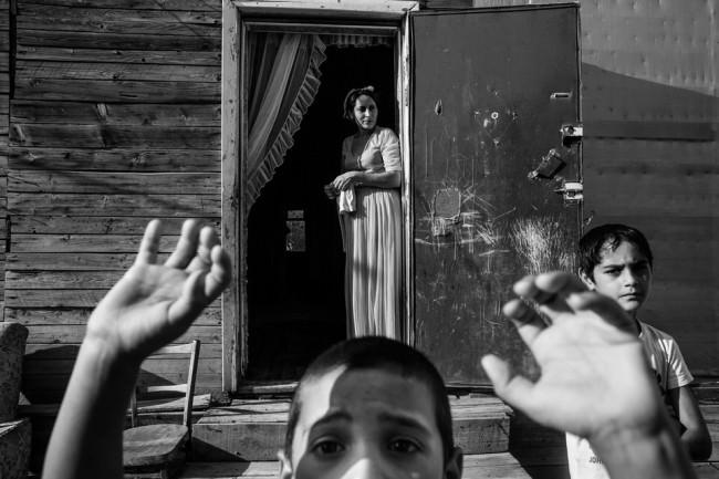 Blick auf einen Jungen im Vordergrund, eine Frau und noch ein Junge stehen im Hintergrund.