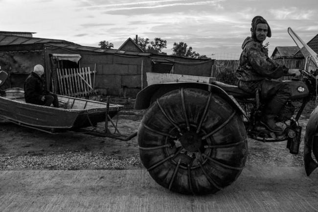 Ein Mann zieht mit seinem Traktor ein Boot.