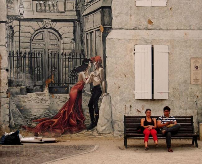 Ein Pärchen auf einer Pank vor einem Wandgemälde
