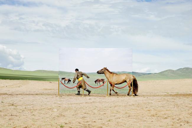 Ein Mann zieht ein Pferd am Zügel hinter sich her