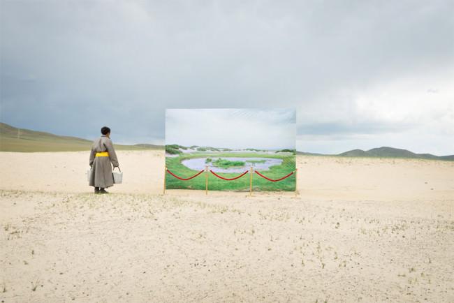 Ein Mensch mit zwei Eimern steht auf einer Sandebene vor einem Bild einer grünen Landschaft mit Wasserloch