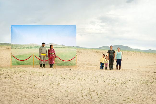 Eine Gruppe modern gekleideter Mongolen steht neben einem traditionell gekleideten Paar.