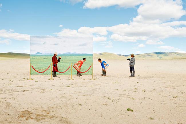 Zwei mongolische Ringer stehen sich mit den Händen auf ihren Knien abstützend gegenüber.
