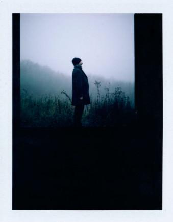 Ein Mann steht im Nebel und schaut nach oben.