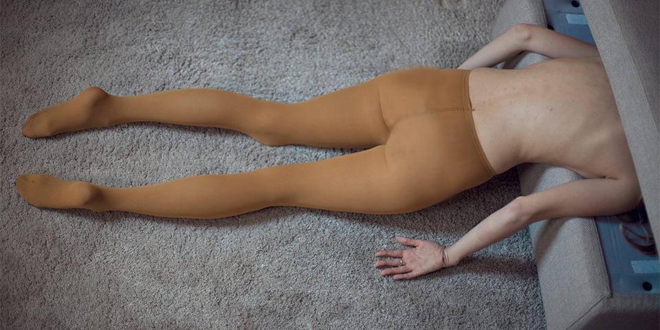 Eine Frau mit dem Kopf im Bettkasten