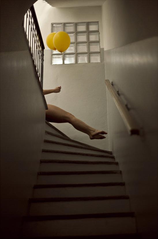 Beine und zwei gelbe Luftballons in einem Treppenhaus