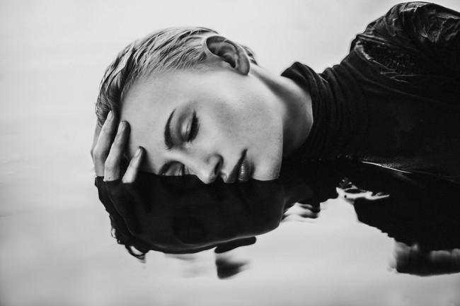 Eine Frau liegt halb im Wasser.